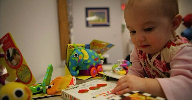 Baby playing with books and toys